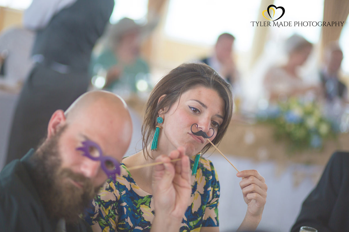 Wedding Guests using props at the table at Worthing Pier Wedding by Kent Wedding Photographer Tyler Made Photography