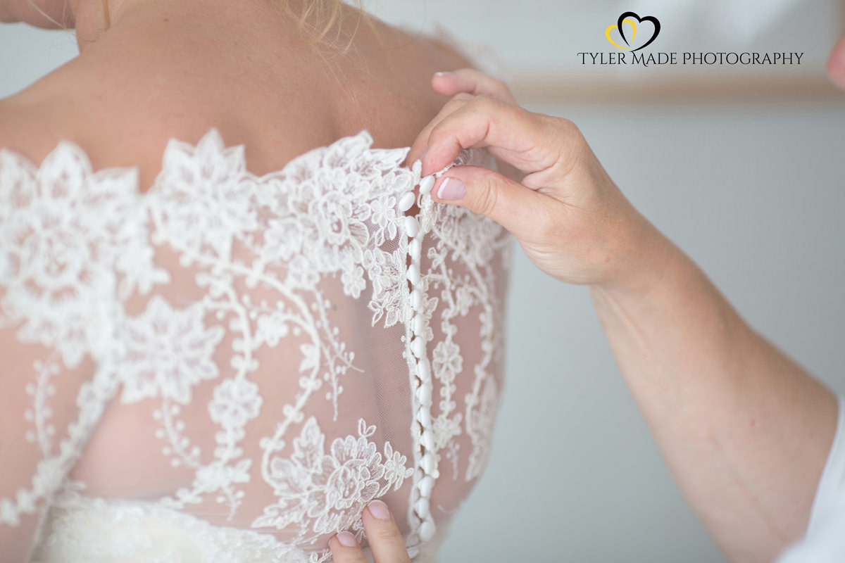 Bride having dress done up by Kent Wedding Photographer Tyler Made Photography