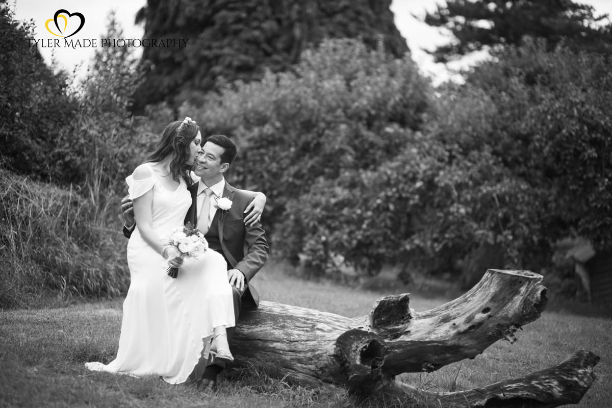 Bride and Groom posing on fallen tree by Kent Wedding Photographer Tyler Made Photography