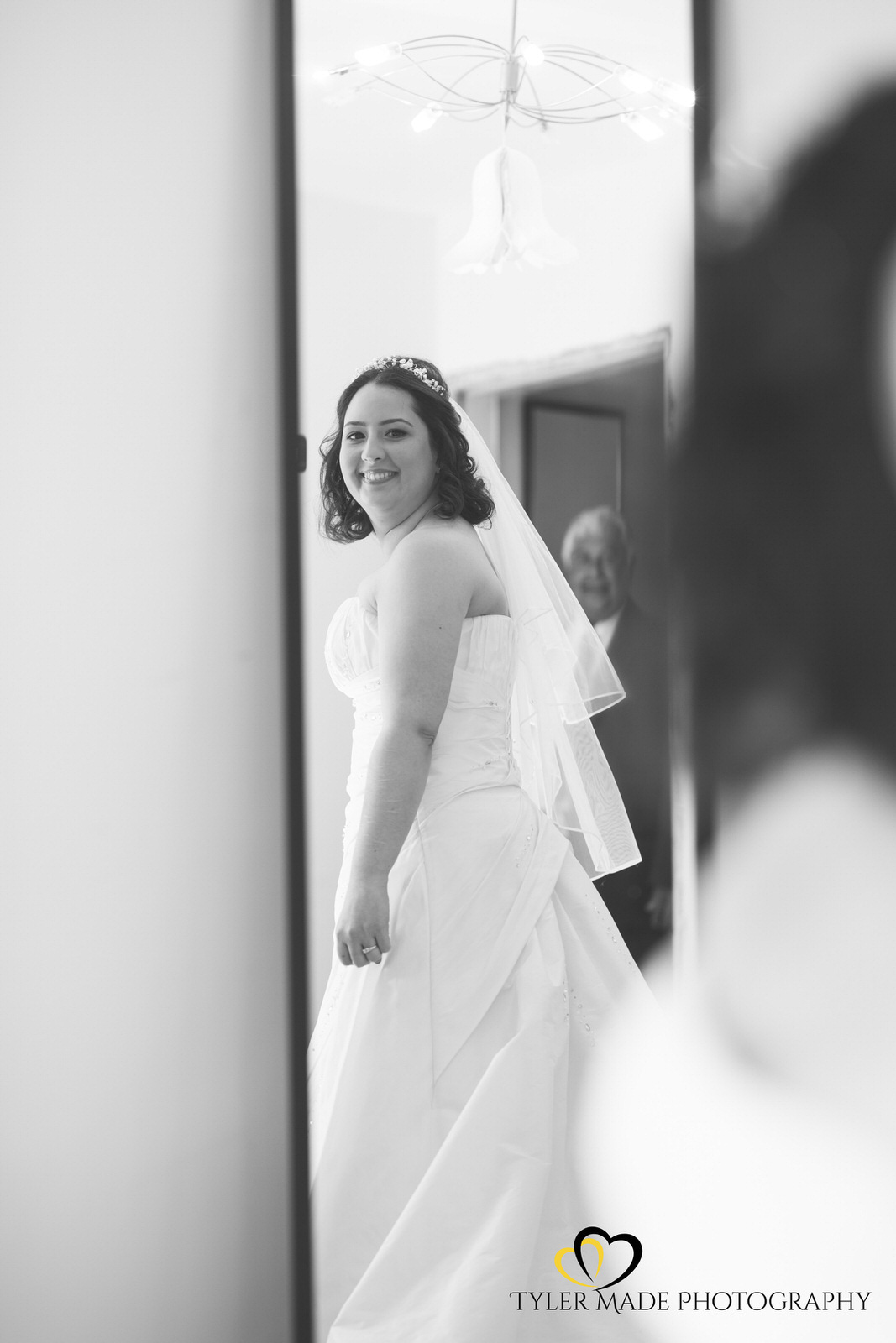 Bride catching a glimpse of herself in the mirror during bridal prep by Tyler Made Photography