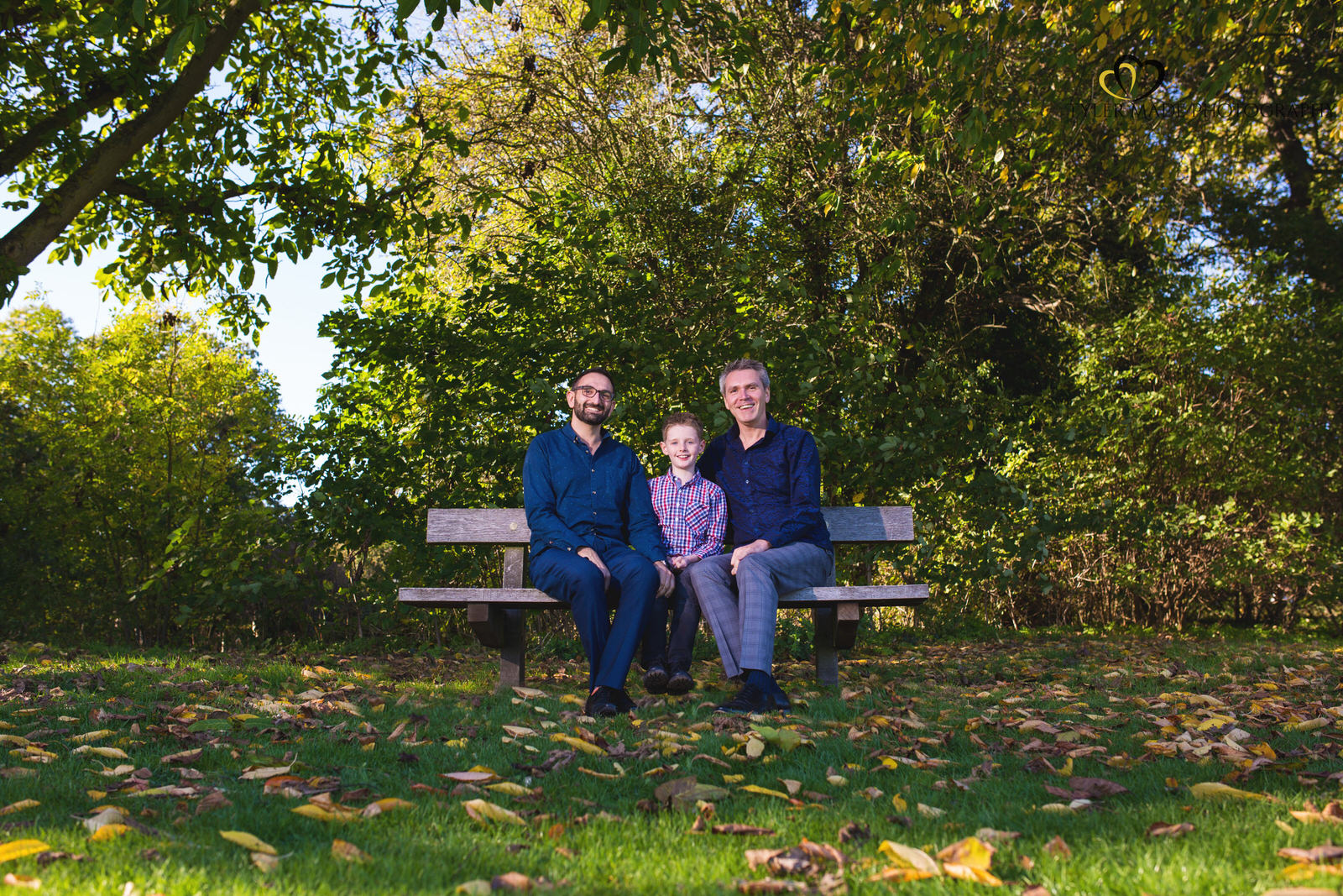 Boy and two dads sitting on a park bench
