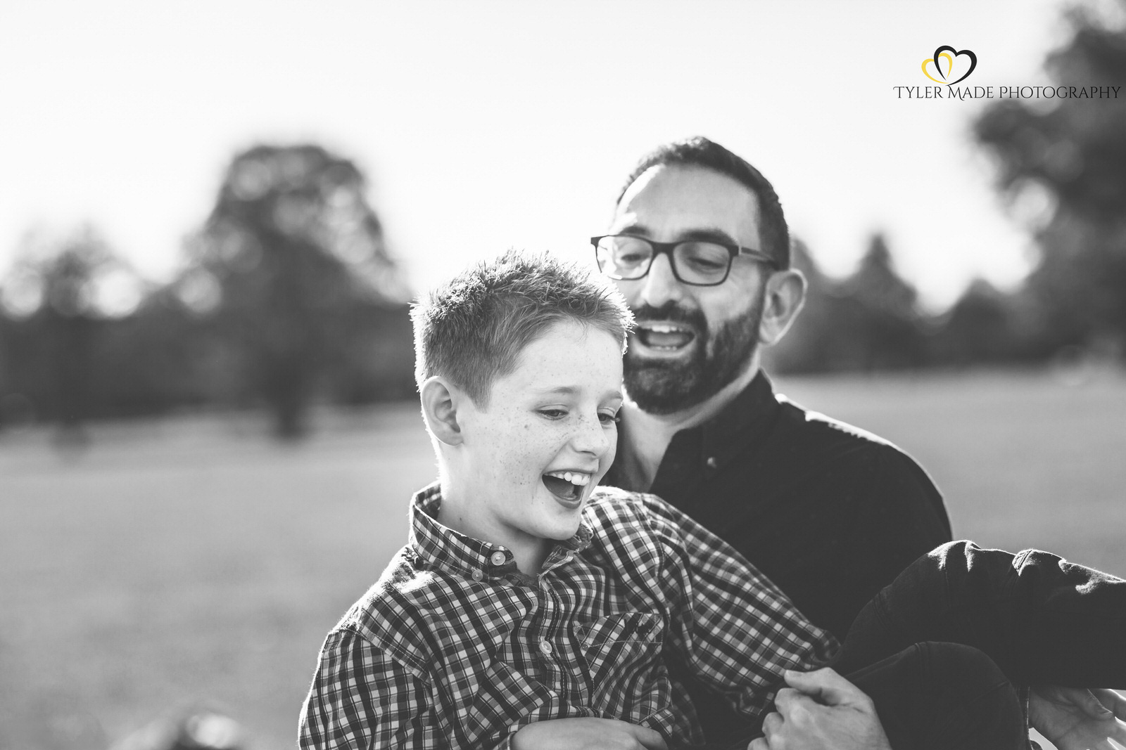 Boy being carried by his dad and laughing by Tyler Made Photography