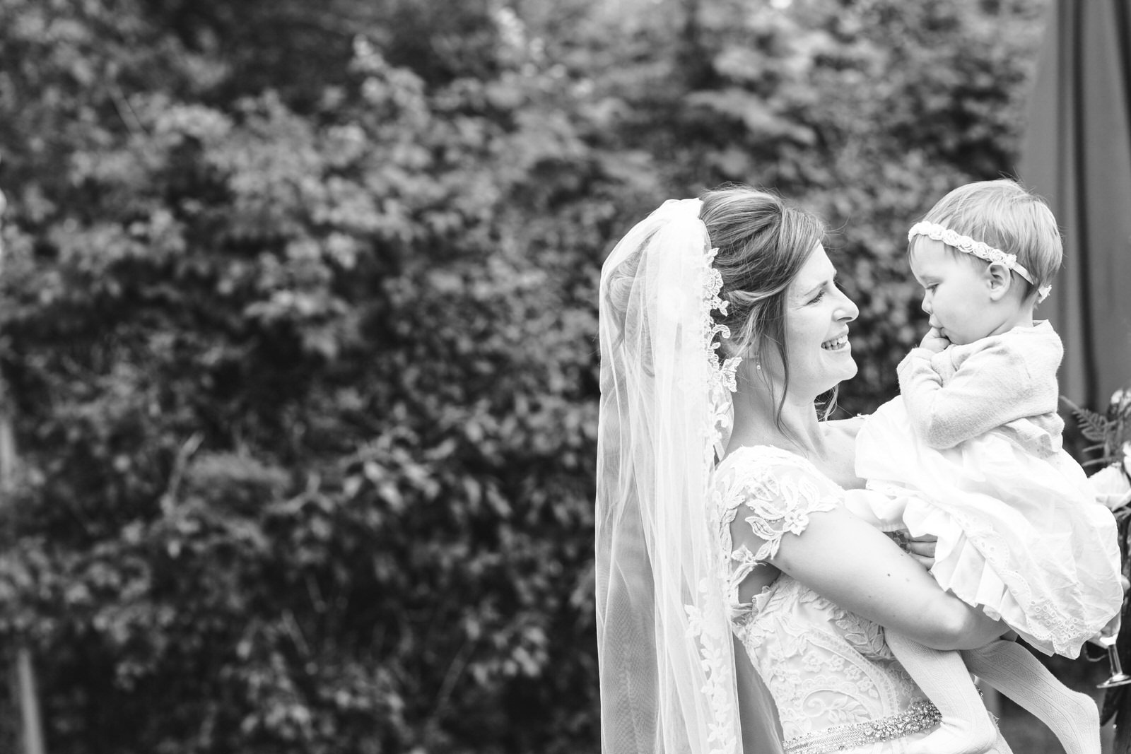 Bride holding baby at wedding by Tyler Made Photography