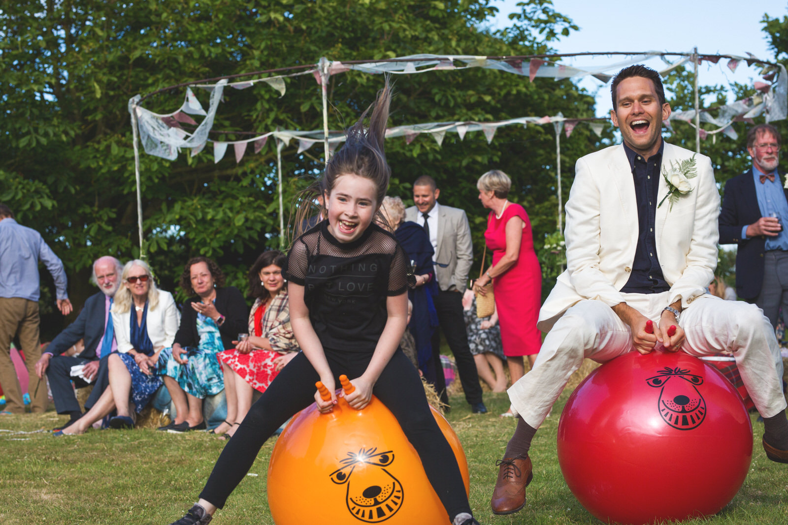 Wedding guests racing on space hoppers by Tyler Made Photography