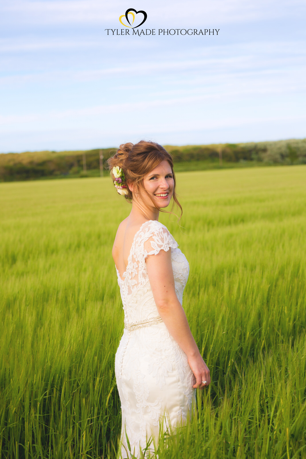 Boho Wedding Bride standing in a field by Tyler Made Photography