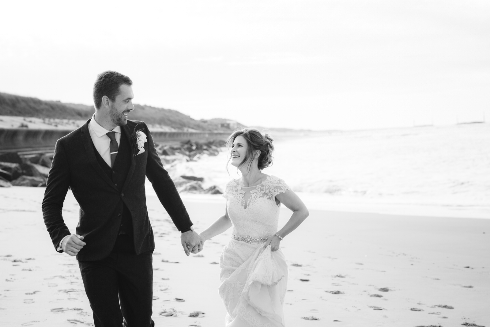 Bride and Groom running and laughing along beach by Tyler Made Photography